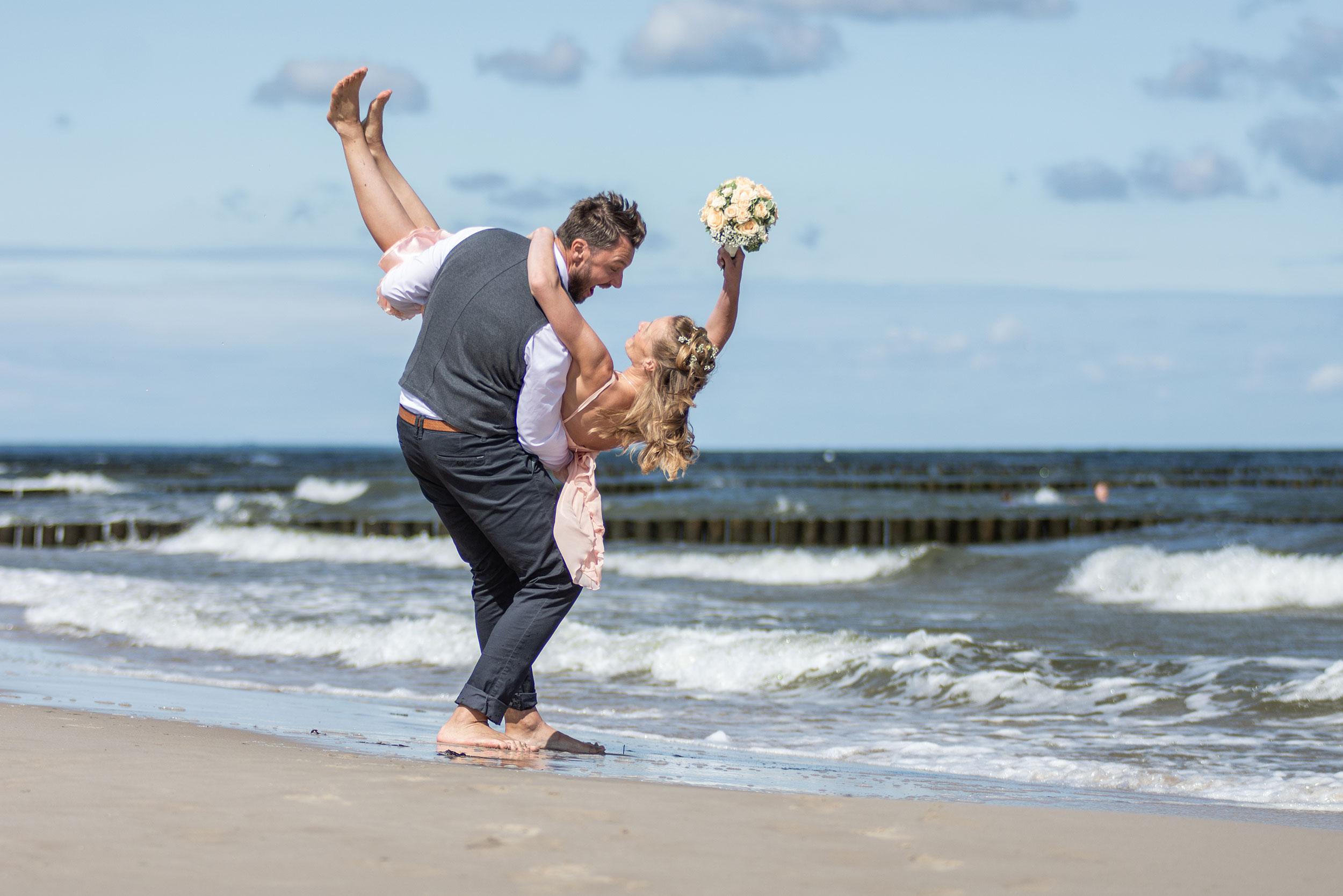 Hochzeitsfoto Brautpaar lacht am Strand lustig