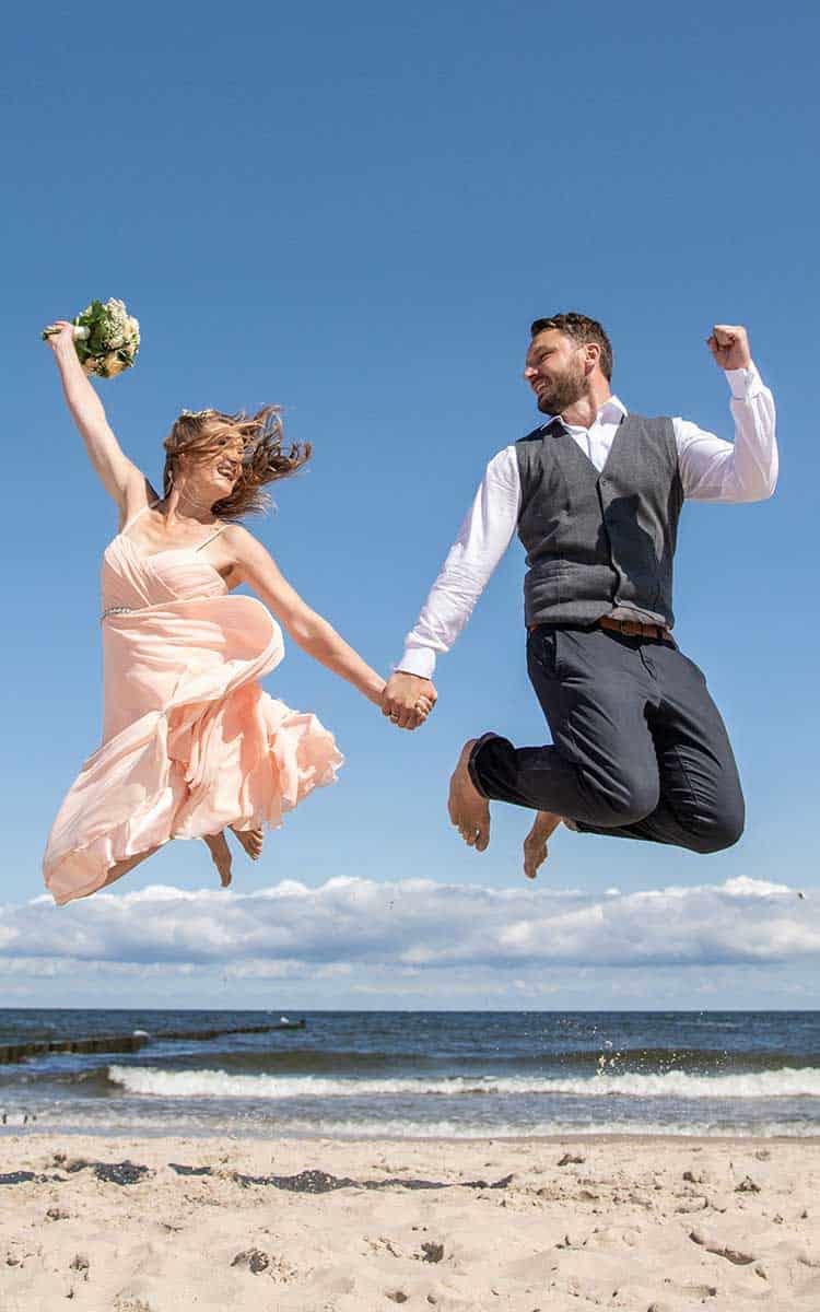Brautpaar springt am Strand