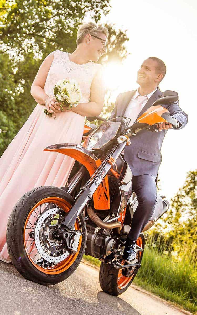 Brautpaar im Gegenlicht mit Motorrad
