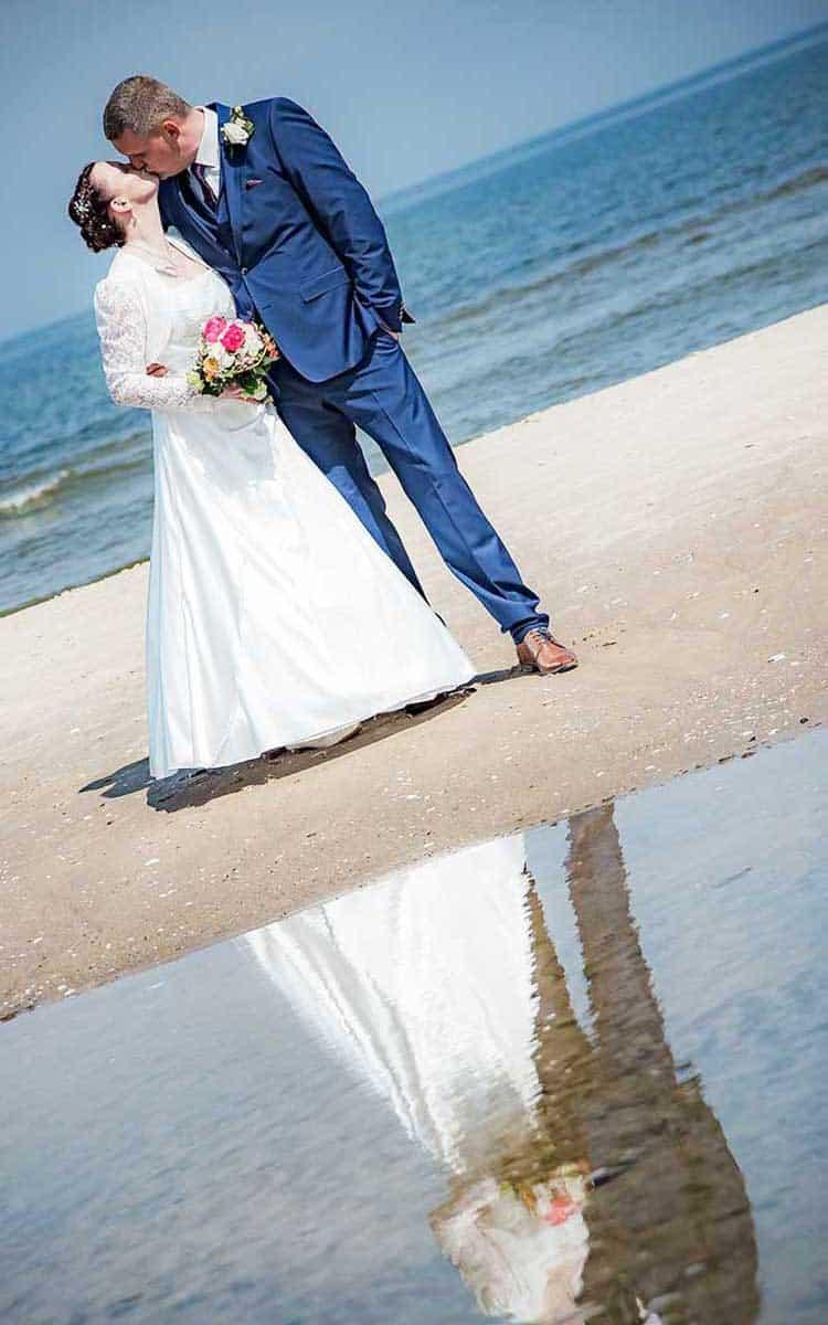 Brautpaar spiegelt sich im Wasser an der Ostsee