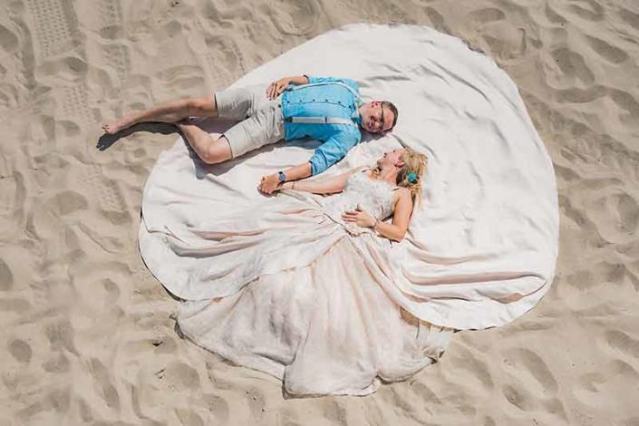 Brautpaar mit riesigen Kleid im Sand