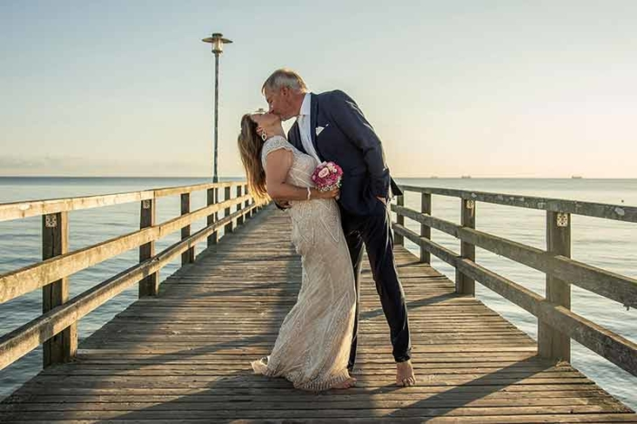 Brautpaar auf Seebrücke zum Sonnenaufgang