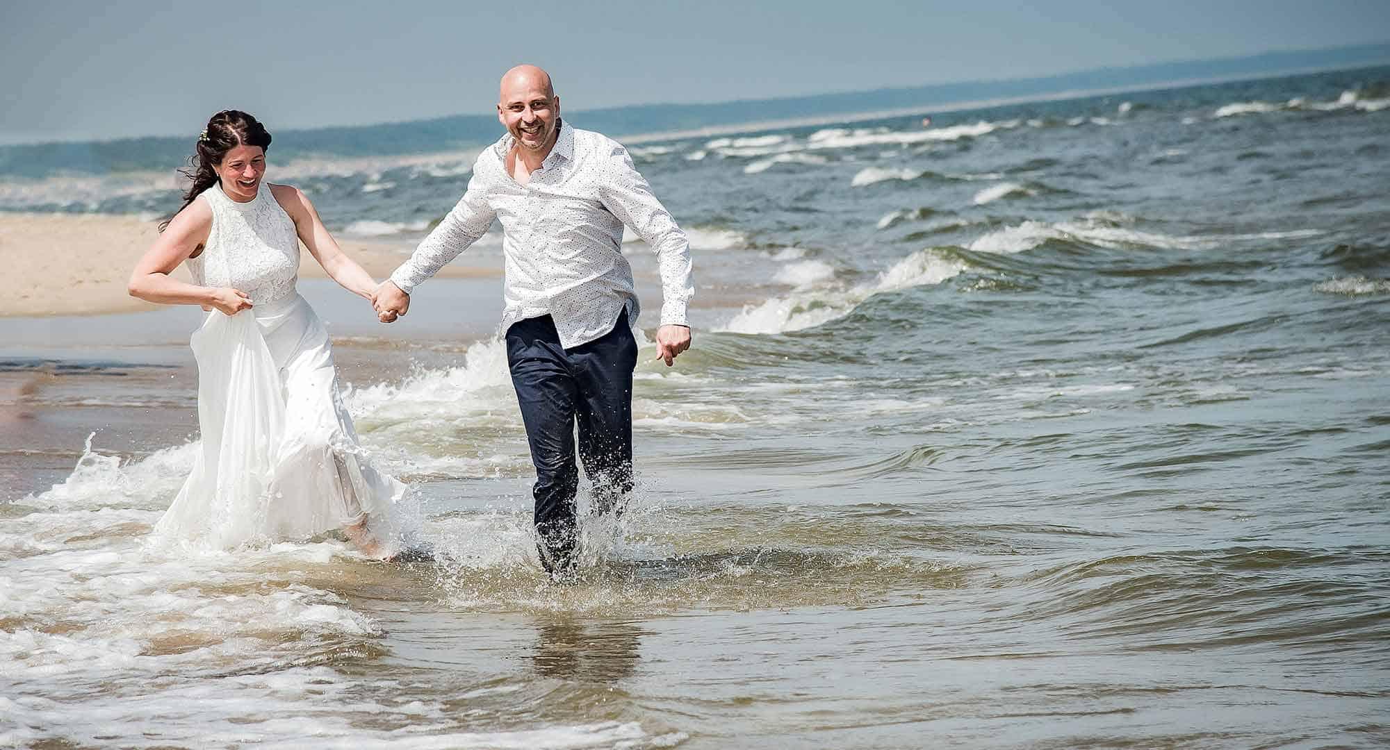 Brautpaar läuft im Wasser