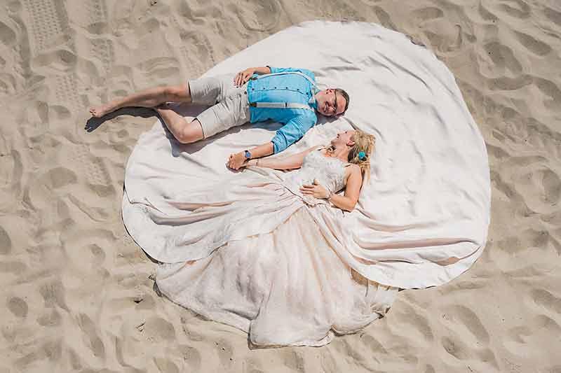 Brautpaar liegt im Sand